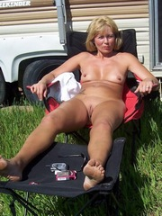 Sexy naked milf sunbathing near the trailer in the camp for nudists